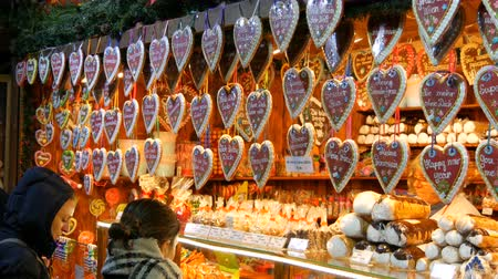 Vienna, Austria - December 21, 2019: Beautiful delicious heart-shaped Christmas gingerbread cookies hang on a kiosk counter. Traditional European Christmas Market. Inscription in german