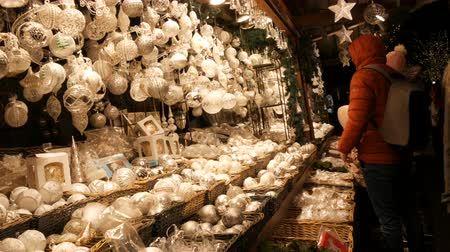 adwent : Vienna, Austria - December 21, 2019: White Glass Christmas toys and decorations balls on counter of Christmas market. Night shot Vienna christmas market