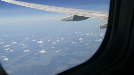 The plane flies over the rare fluffy clouds. Fields of Europe view from the porthole on wing of the aircraft