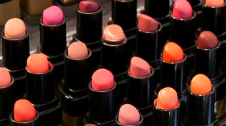 потребитель : Shop luxury fashion cosmetics. Stands with variety of different color lipsticks, professional women cosmetics