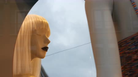 poppetjes : Part of a womans mannequin with white long hear near the mirror. Dummy in shop window. Beautiful, expensive, fashionable clothes are shown on a boutique showcase