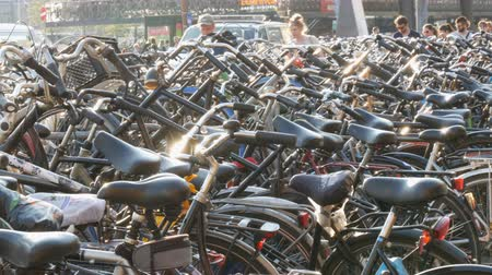 bikers : Amsterdam, Netherlands - April 21, 2019: Parking for bicycles. Many different bicycles parked on a street in special parking lots. The problem of bicycle overload in the country Stock Footage