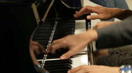 симфония : Playing the piano in four hands. Masterly pianists play at central railway station in Amsterdam