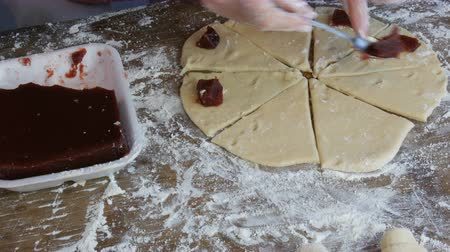 pastelaria : Female hands lay with a teaspoon in a circle slices of cherry jam on raw dough for future croissants. Homemade sweet pastries. Jam, the dough, made by woman hand at home kitchen Stock Footage