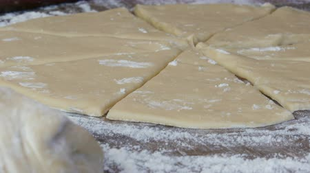 basic shape : Female hand cuts the dough with a knife. Homemade sweet pastries at home kitchen