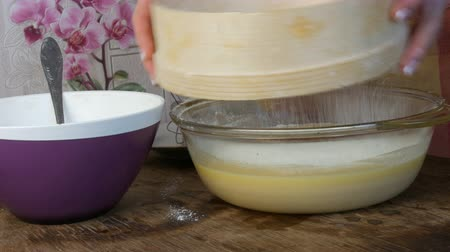 fondán : Female hands sift flour through a special sieve in the home kitchen. Future home baking dough