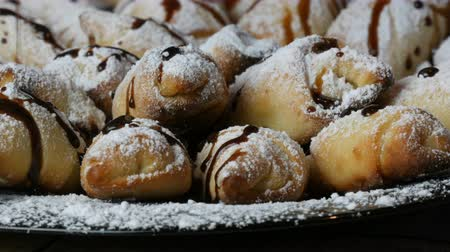 tereyağlı : Freshly baked homemade croissants with icing sugar on top poured with chocolate icing on a large plate in the kitchen