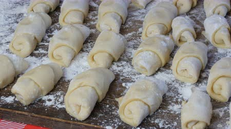 pasta cutter : Homemade pastries, freshly made buns, croissants and other fresh pastry are in a row on the table in the home kitchen, ready for baking in the oven Stock Footage
