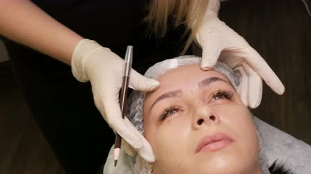 по уходу за кожей : The master draws a new shape of the eyebrows with special pencil. Eyebrow shape correction. Microblading, permanent makeup, tattoo