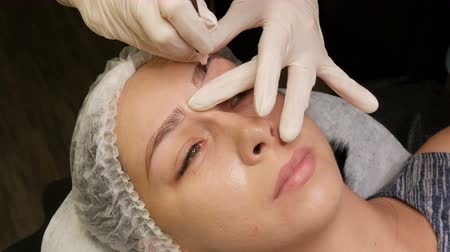 apply : The master draws a new shape of the eyebrows with special pencil. Eyebrow shape correction. Microblading, permanent makeup, tattoo