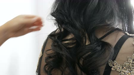 Professional woman hairdresser combing comb with long black curls of a young beautiful woman who is sitting from the back in a festive evening dress Stock Footage