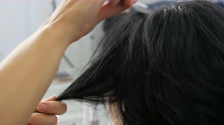 Woman hairdresser combing long black curls with a comb. Hairdresser combing hair strand while hairstyling in beauty salon. Make hairdo for long haired woman. Beauty concept