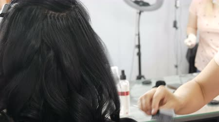 rolki : Professional woman hairdresser combing comb with long black curls of a young beautiful woman who is sitting from the back in a festive evening dress Wideo