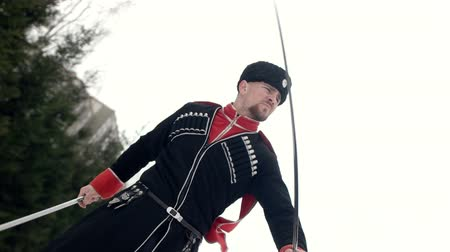 ruský : A young man in Cossack clothes swinging a sword in a winter landscape in the snow. Dostupné videozáznamy
