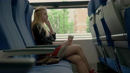Young attractive woman sits in train car. Girl drinking coffee in train