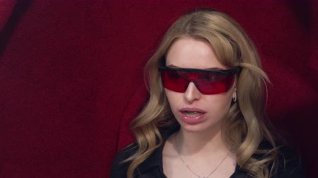 Young blonde girl puts on protective glasses getting UV whitening. Before the procedure of teeth whitening.