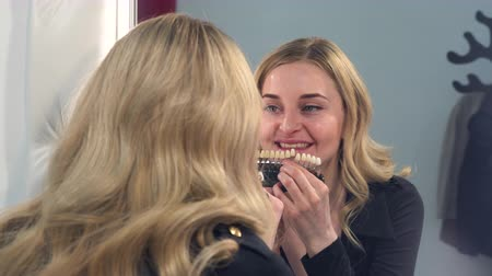 A blonde girl looks at the result front of the mirror of teeth whitening on a special color scale. The girl is happy with the result.