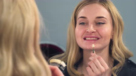 A blonde girl looks front of the mirror at the result of teeth whitening on a special color scale. The girl is happy with the result. Stock mozgókép