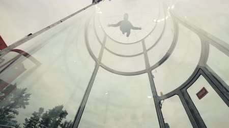 Man skydiver flies in wind tunnel. Indoor skydiving wind tunnel