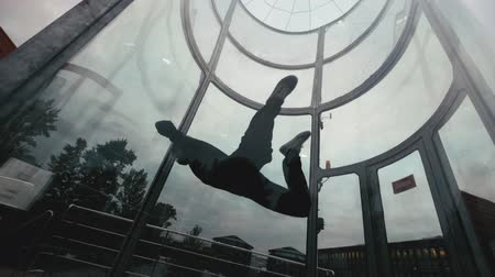 Man skydiver flies in a circle in wind tunnel. Flying in a wind tunnel