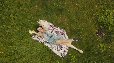 Sky view beautiful young woman lying on grass in summer day Stock mozgókép