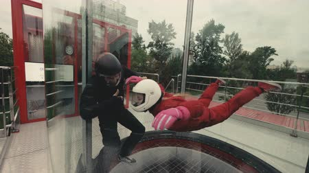 Woman flying in wind tunnel. Indoor skydiving wind tunnel