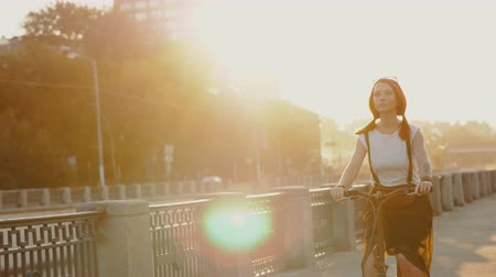 Red haired woman riding a bicycle on background sunlight in city
