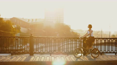 Young woman riding bicycle in city bridge on background golden rays sun Stock mozgókép