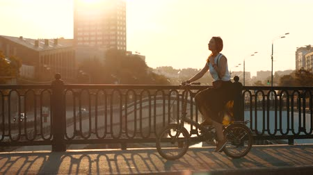 Young woman riding bicycle in city bridge on background buildings and sun Stock mozgókép