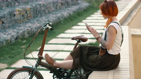 Redhaired woman cyclist making selfie on mobile phone with bike. Woman bicycling Stock mozgókép