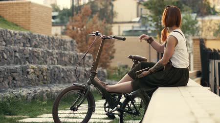 Redhaired woman cyclist sitting on bench and putting feet on bicycle.