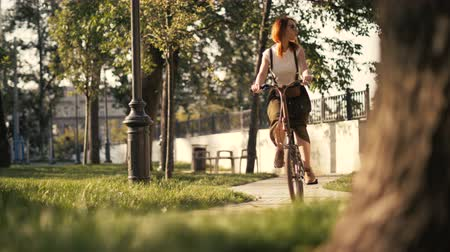 Young woman with red hair riding a bike in park bottom view. Woman bike park Stock mozgókép