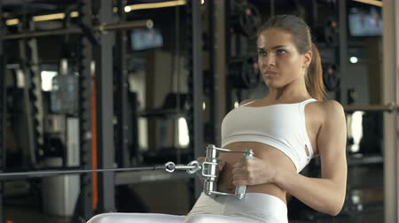тянущий : Strong woman lifting weights on training equipment in fitness club