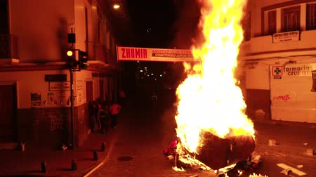 yaklaşım : Cuenca, Ecuador - December 31, 2018 - Street bonfire at midnight gets too hot to approach on New Years Eve Stok Video