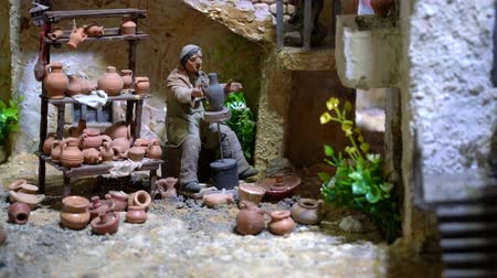jesus born : Cuenca, Ecuador - January 3, 2019 - Largest animated nativity scene in South America. Potter makes pots from clay on a spinning wheel.