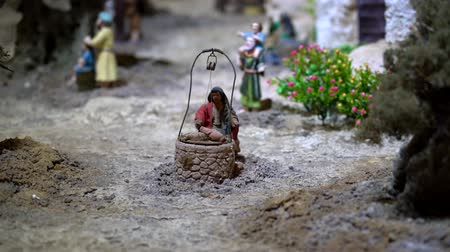 moudrý : Cuenca, Ecuador - January 3, 2019 - Largest animated nativity scene in South America. Woman retrieves water from a well.