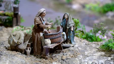 jesus born : Cuenca, Ecuador - January 3, 2019 - Largest animated nativity scene in South America. Woman gives baby a bath in a bucket.