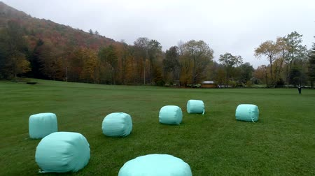 balé : Aerial Drone - Fly Over Plastic Wrapped Bales of Hay in Fall in Vermont.
