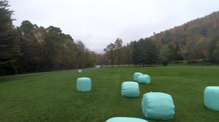 balé : Aerial Drone - Skim Slowly Over Plastic Wrapped Bales of Hay in Fall in Vermont.