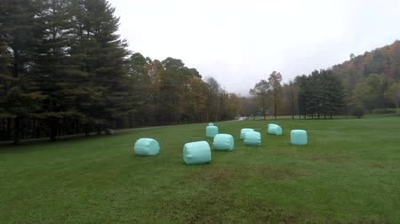 packing hay : Aerial Drone - Fly Over Field With Plastic Wrapped Bales of Hay in Fall in Vermont. Stock Footage