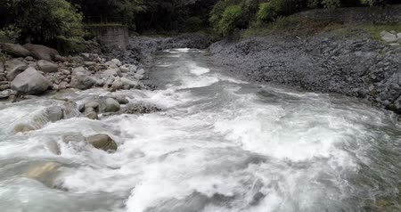 upstream : Banos, Ecuador - September 24, 2018 - Drone Backs Up White Water of River at Low Altitude
