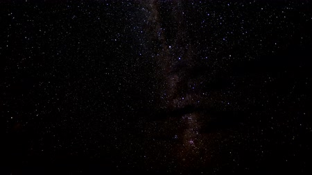 astro : Milky Way moves through sky as some clouds pass over front Stock Footage