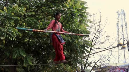acrobata : Nandgeon, India - 20180225 - Girl Crosses Slackroap to Entertain Passing Crowd