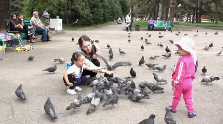 hoe : Almaty, Kazakhstan - 20170531 - Mother teaches daughter how to feed pigeons in park