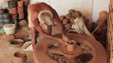 moldagem : Madurai, India - 20180310 - Man Uses Fully Manual Potter Wheel  -  Completes Second Base Pot