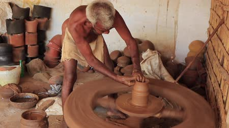 kamenina : Madurai, India - 20180310 - Man Uses Fully Manual Potter Wheel  -  Wets Clay And Starts Cutting