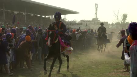 worship : Anandpur Sahib, India - 20180302 -  Hola Mohalla  -  Sikh Festival  -  Horsemen Race Past Crowd Stock Footage
