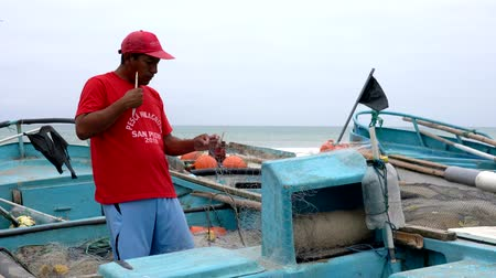 ügyesség : San Pedro, Ecuador - 20180915 -  Man in Red Shirt Cuts Net to Repair It