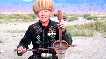 kul : Issyk Kul, Kyrgyzstan  -  20170528  -  Man Plays Traditional Komuz Two Stringed Instrument Stock Footage