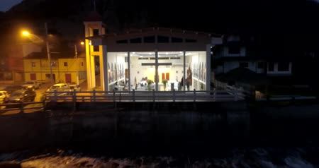 barışçı : La Entrada, Ecuador - 20180914 - Drone Aerial  -  Drone Pulls Rapidly Away From Glass Fronted Church With People Inside at Night at High Tide Stok Video